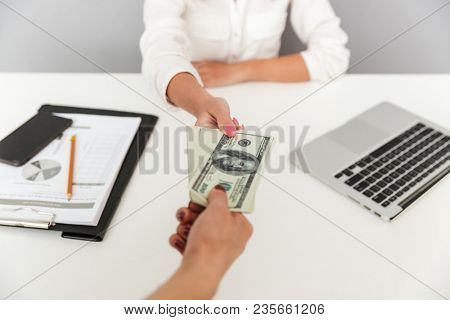 Close up portrait of hand holding cash bribe in front of a female office worker isolated. Businesswoman taking the bribe
