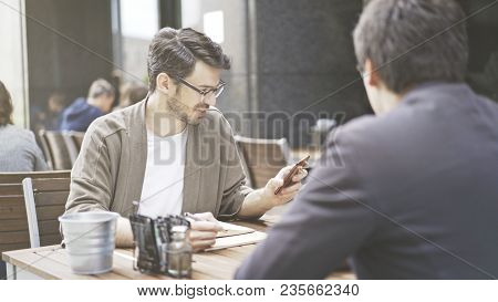 A Man In Eyeglasses Holding Looking At The Phone At Cafe Outdoors. A Man Dressed In A Jacket Wearing