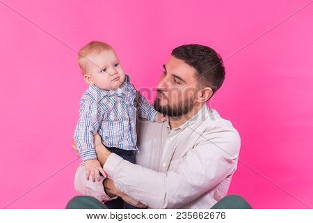 Baby In The Daddy Hands. Pink Background