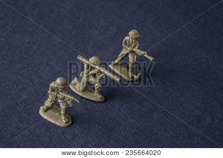 Miniature Toy Soldiers On Blue Background. Plastic Toy Military Men At War.