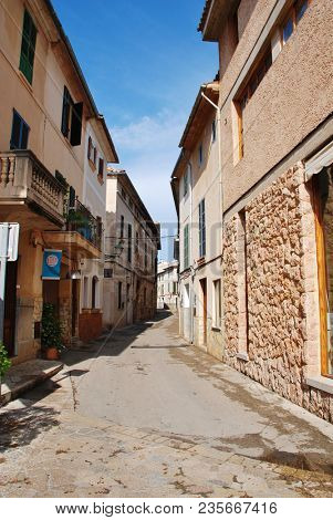 MAJORCA, SPAIN - SEPTEMBER 4, 2017: A narrow shaded street in the old town of Pollensa on the Spanish island of Majorca. The historic town is a popular tourist destination.