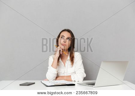 Portrait of a pensive young business woman sitting at the office desk isolated over white background