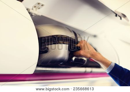 Hand-luggage Compartment With Suitcases In Airplane. Hands Take Off Hand Luggage. Passenger Put Cabi