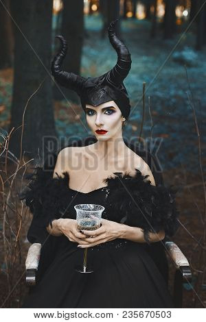 Beautiful And Fashionable Brunette Slim Model Girl In The Image Of Maleficent With Wine Glass In Her