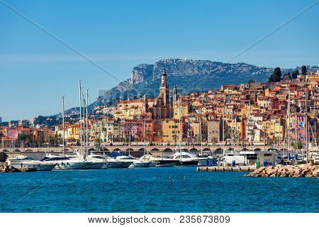 View of small harbor with yachts and old colorful houses of the Old Town on background in Menton - popular tourist resort on French Riviera.