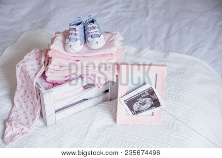 Children's Shoes And Clothes On The Bed. Beautiful Pink Baby Clothes. Newborn. Home Cosiness. Baby.