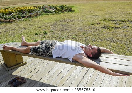 Man Is Lying On A Bench And Stretching. A Smile On The Face Of A Man Lying On A Bench