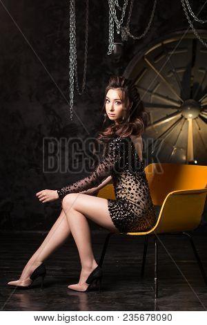 Sexy Brunette Woman In Evening Cocktail Dress In Dark Studio Interior.
