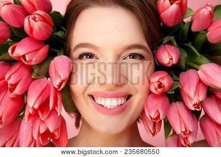 Headshot Of Young Cheerful Woman And Pink Tulips Around