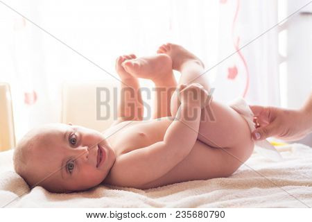 Hygiene - young mom wiping the baby skin with wet wipes carefully. Cleaning wipe, pure, clean