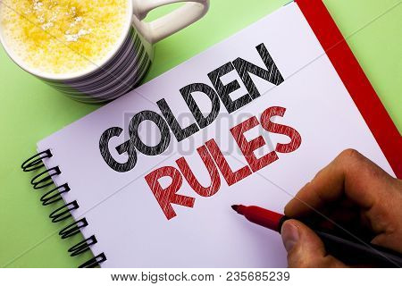 Word writing text Golden Rules. Business concept for Regulation Principles Core Purpose Plan Norm Policy Statement written by Man Notebook Book Holding Marker the plain background Coffee Cup poster