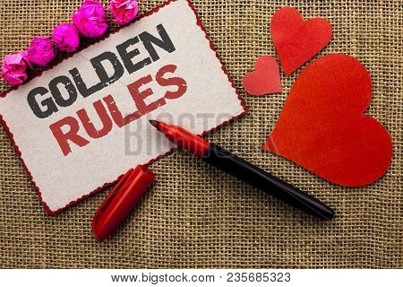 Word writing text Golden Rules. Business concept for Regulation Principles Core Purpose Plan Norm Policy Statement written Cardboard Piece the jute background Marker and Hearts next to it. poster