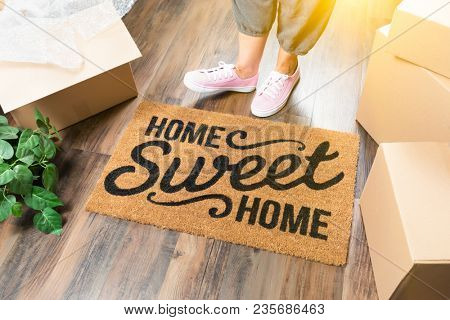 Wman in Pink Shoes and Sweats Standing Near Home Sweet Home Welcome Mat, Boxes and Plant.