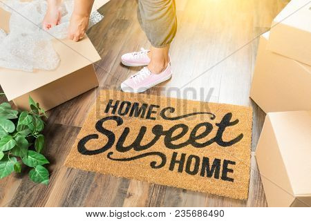Wman in Pink Shoes and Sweats Unpacking Near Home Sweet Home Welcome Mat, Moving Boxes and Plant.