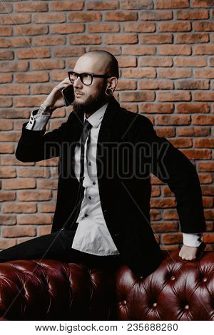 Portrait of a businessman in elegant classic suit and piercing in the ears and lips talking on the phone. Men's beauty, fashion.