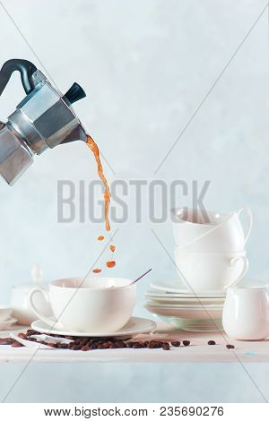 Pouring Coffee From A Moka Pot Into A Porcelain Cup. White On White Still Life With A Kitchen Shelf,