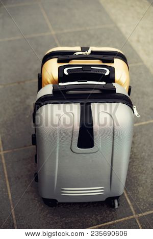 Two Suitcases On Grey Blurred Background. Summer Vacation And Travel Concept. Traveler Suitcase With