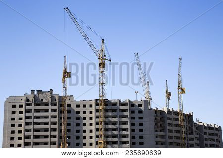 Distant View Of A Construction Site With An Unfinished Apartment Building And Several Cranes. Clear