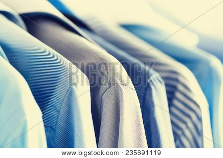 Male Clothes, Jackets And Shirts Hanging On Clothes Rail. Blue Color Clothes. Copy Space. Image With