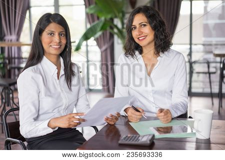 Two Happy Female Colleagues Working With Documents In Cafe. They Are Sitting At Table And Looking At
