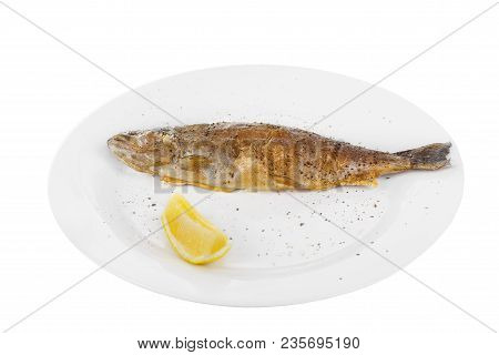 Fish Trout Whole With A Head Baked Fried Over An Open Fire With A Slice Of Lemon And Ground Pepper.