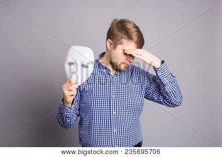 Young Man Taking Off Plain White Mask Revealing Face