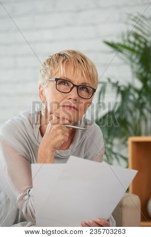 Portrait Of Thinking Aged Woman With Documents