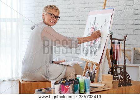 Senior Smiling Woman Enjoying Painting At Home