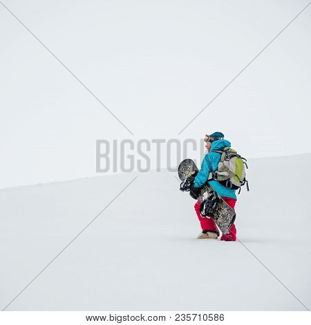Pretty Young Woman Hiking With Snowboard In The Mountains