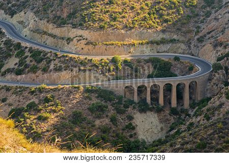 Aerial above view of a rural landscape with a curvy road running through it in Spain, Andalusia poster