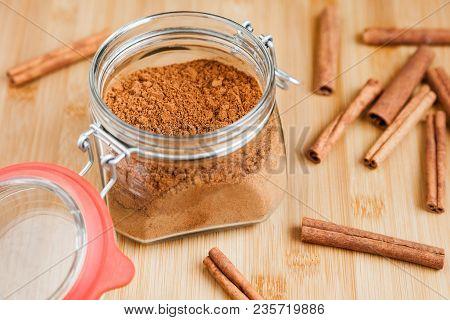 Glass Jar With Cinnamon Powder And Several Cinnamon Sticks Close-up