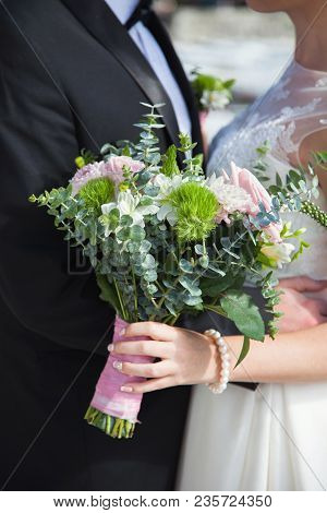 The Bride And Groom Hug Near Sea, Hold Wedding Bouquet From Pink Roses, Eucalyptus And Dahlias Flowe