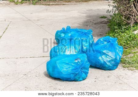 Garbage On The Urban Street In Blue Plastic Bags Polluting The City With Junk And Litter