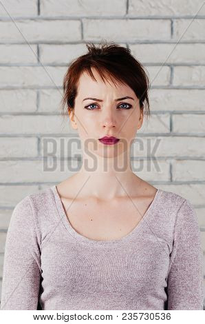 A Pretty Girl With A Frowning Face, Big Blue Eyes, Full Pink Lips, With White Brick Wall In The Back