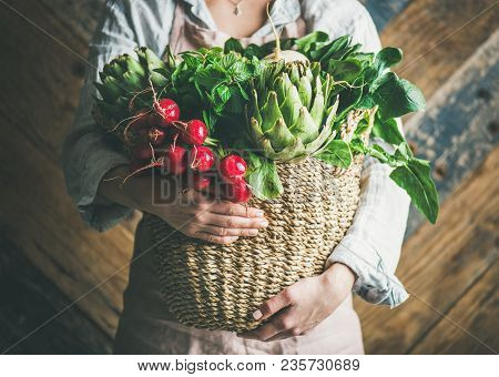 Female Farmer In Linen Apron Holding Basket Of Fresh Garden Vegetables And Greens In Her Hands, Rust