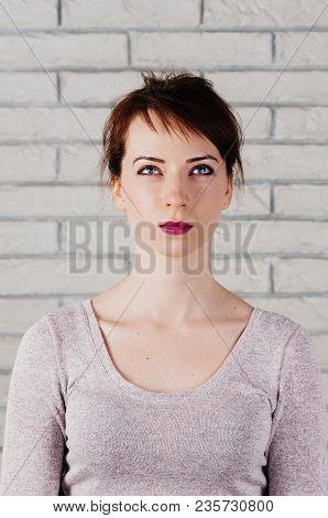 A Pretty Girl With Face Mimic For Fitness Exercise, Eyes Squinched And Looking Upward, Mouth Closed,