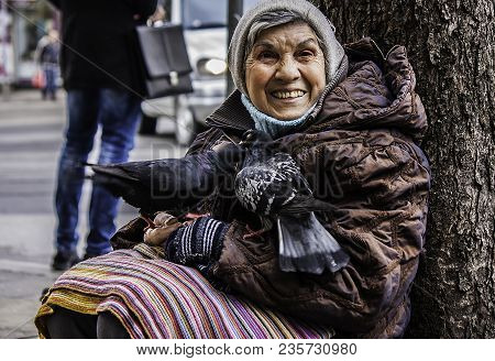 Poor Homeless Woman Begs Money From Street People And Lives With Urban Birds In Sofia/bulgaria/03.20