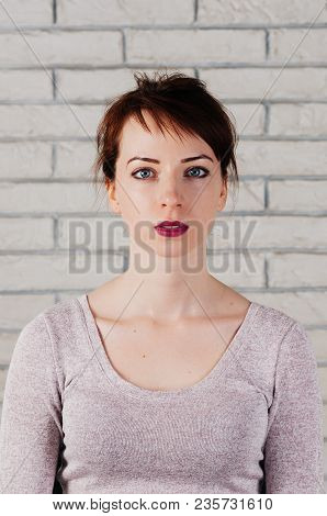 A Pretty Girl With Perplexed Face, Big Opened Eyes, Pink Lips, With White Brick Wall In The Backgrou