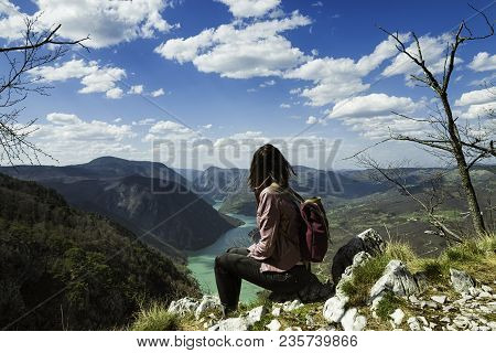 Girl relaxing on a beautiful mountain view. Traveler sitting on mountain rock enjoying beautiful mountain view.  Traveler. Travel. Mountain view. Mountain peak. Outdoor traveler. Backpack traveler. Traveling alone. Hipster traveler.