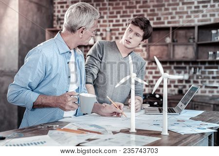 Project For Two. Thoughtful Reflective Male Engineers Discussing Project While Creating Blueprints A