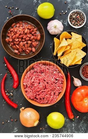 Ingredients for cooking Mexican chili con carne dishes on a black concrete background, top view