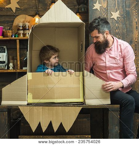 Boy Play With Dad, Father, Little Cosmonaut Sit In Rocket Made Out Of Cardboard Box. Kid Happy Sit I