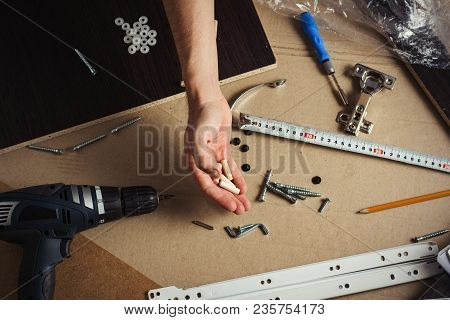 Hands Of A Man With A Tool. Screwdriver, Screws, Furniture Details. Concept Workshop. Flat Lay, Top