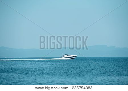 High Speed Boat In Sea, Blue Sky And Mountains On Background. Amazing View On White Luxury Yacht Gli