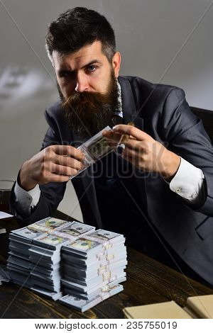 Man Sitting At Table With Piles Of Money, Counting Profit. Illegal Cash Concept. Businessman On Seri