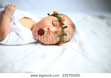 Portrait-serene Newborn Baby On A Bed Yawning.the Photo Has A Empty Space For Your Text