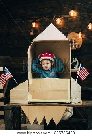 Boy Play With Rocket, Cosmonaut Sit In Usa Rocket Made Out Of Cardboard Box. Kid In Helmet Sit In Ca