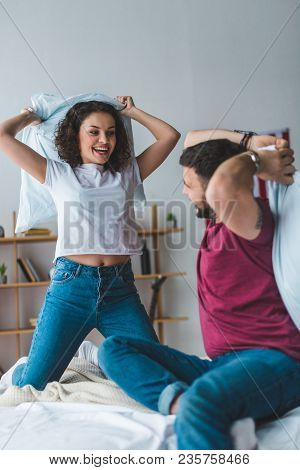 View Of Smiling Couple Fighting By Pillows On Bed