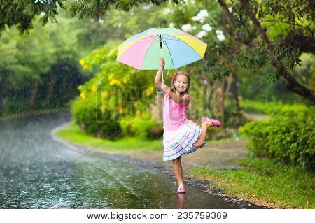 Kid Playing Out In The Rain. Children With Umbrella Play Outdoors In Heavy Rain. Little Girl Caught