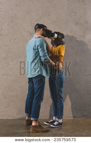 Side View Of Couple Holding Each Other And Using Virtual Reality Headset